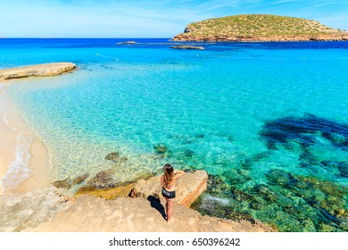 Unidentified young woman in swimsuit standing on a rock and posing against beautiful Cala Comte beach, Ibiza island, Spain