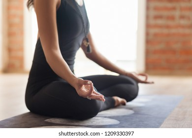 Unidentified young woman yoga instructor meditates In an empty bright room sitting in the lotus position. Concept of relaxation and exercise training