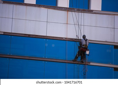 Unidentify rope access repairer construction worker working on ropes, using descend devise abseiling, wearing protection full body harness, black helmet on building site in Sydney city CBD, Australia