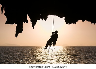 Unidentify rope access worker abseil of the cliff at sunrise in Phang Nga bay,  southern of Thailand