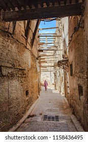 Unidentifyable woman in kaftan, berber clothing walking on a narrow street in Fes Medina in Morocco