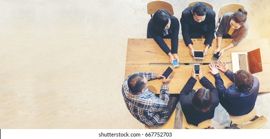 Unified Collaboration Marketing Team Collaborate in office meeting. Group of people using smartphone working Sales Team. Marketing communications strategy in business office. Banner with copy space.