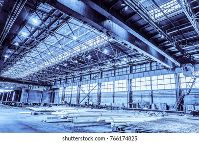 Unified standard typical span prefabricated of a steel frame production building. Industrial metalwork production hall with overhead cranes. Background in blue tone