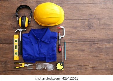 Uniform and construction tools on wooden table, top view