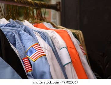 Uniform shirts for blue-collar workers on a clothing rack at a second hand store.