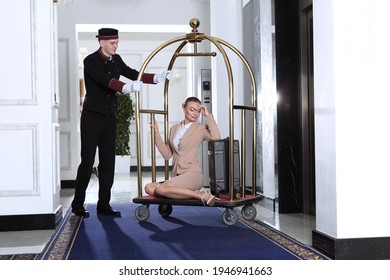 A uniformed doorman pushes a luggage cart toward the elevator.A young woman sits on a luggage cart.Hotel service.The holiday season. business woman on a business trip.