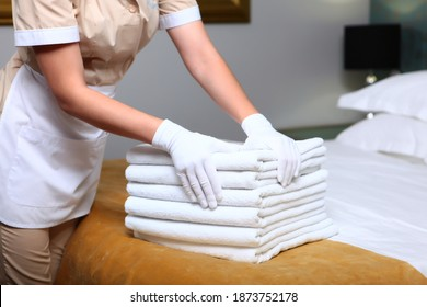 A uniformed maid changes towels in the hotel room. Cleaning at the hotel. The concept of the hotel business. Unrecognizable person. Photos inside the room. Copy space.