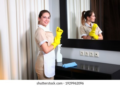 Uniformed maid wears yellow protective gloves. Reflection in the mirror. Hands in protective gloves. Cleaning and disinfection of the hotel. The concept of the hotel business.