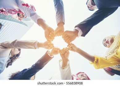Unify collaboration work group with multirace team bumpping hands together in the meaning of teamwork. Multiethnic people team collaborate working community in angle view. Unified Friendship Concept