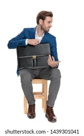 Unimpressed businessman holding his briefcase and disagreeing while looking to the side, wearing a suit and sitting on a chair on white studio background