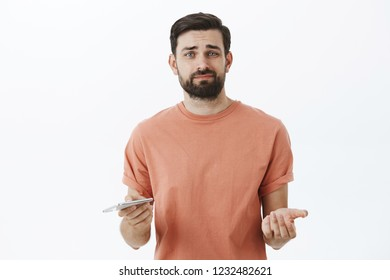 Unimpressed and displeased guy holding smartphone feeling displeased after using new device thinking gadget useless smirking from dislike and raising palm in clueless gesture over gray wall