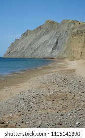 Uninhabited sea shore. A mountain of clay is foreground.