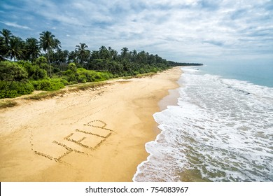 Uninhabited and wild tropical island with a deserted beach. Sand with the inscription HELP. The lost in the sea calls for help. Aerial panoramic view of a sandy shore with coconut palms in tropics.