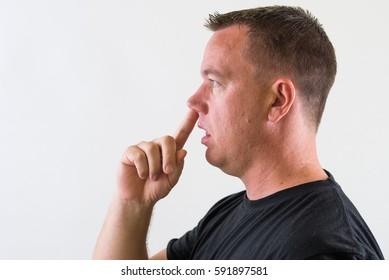 Unintelligent man picking his nose.