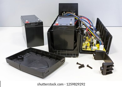 Uninterruptible power supply that is open for battery replacement. Repair and maintenance of UPS. Replacing 12 volt battery.