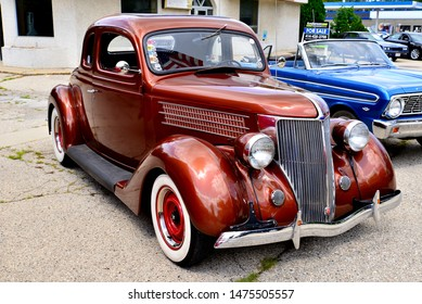 Union Grove, Wisconsin / USA - August 10, 2019: A lovely brown metallic 1936 Ford Coupe with the tall standing identifiable grille at the local car show on a warm summer afternoon.