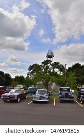 Union Grove, Wisconsin / USA - August 10, 2019: Old antique car Studebaker Commando and a Pontiac GTO lined up at a car show with the Union Grove water tower in the background at a summer car show.