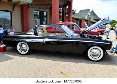 Union Grove, Wisconsin / USA - August 10, 2019:  The side view of an all black Studebaker Commander with hood raised at a local car show on a beautiful mid summer afternoon.