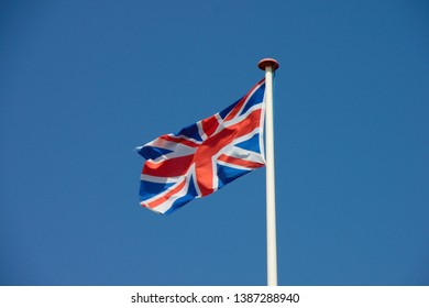 Union Jack, flag of the united kingdom flapping in the wind. Blue sky in the background.