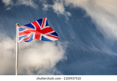 Union Jack flying in the wind on a flagpole with blue skies on a sunny day