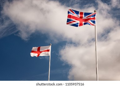 Union Jack and George Cross flags on flagpoles with blue skies on a sunny day