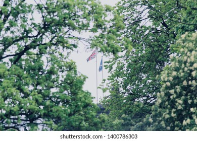 Union Jack and Scottish Saltire Flag on Masts Seen in a Gap in Tree Leaves in Edinburgh