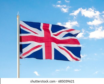 Union Jack, traditional United Kingdom flag, waving in blue sky, copyright space