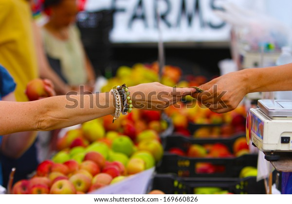 """Union Square Greenmarket, one of New York City's largest & best established direct markets for producers. Man's arm passing over bag of produce with """"FARMS"""" sign out of focus in the background"""