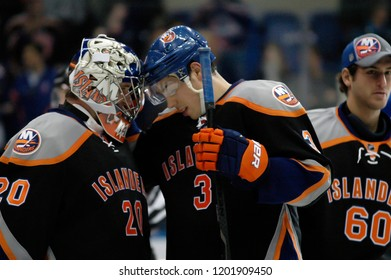 UNIONDALE, NEW YORK, UNITED STATES – March 9, 2013: NHL Hockey: Travis Hamonic and Evgeni Nabokov, of the New York Islanders, celebrate winning against the Washington Capitals at Nassau Coliseum.