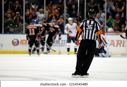 UNIONDALE, NEW YORK, UNITED STATES – March 9, 2013: NHL Hockey: Referee Dean Morton looks on as the New York Islanders celebrate scoring a goal against the Washington Capitals at Nassau Coliseum.