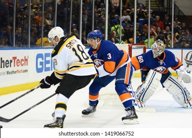 UNIONDALE, NEW YORK, UNITED STATES – Nov. 2, 2013: NHL Hockey: Game action between the Boston Bruins and New York Islanders at Nassau Coliseum. Reilly Smith. Travis Hamonic. Goalie Kevin Poulin.