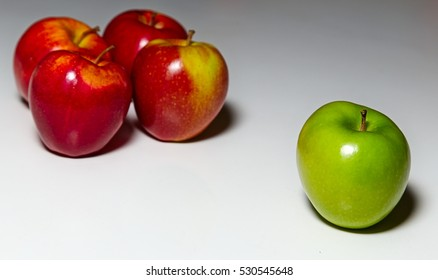 Unique. 4 red apples and 1 green apple on a white surface. One of a kind. Social Exclusion. Being different.