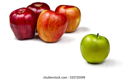 Unique. 4 red apples and 1 green apple on a white surface. One of a kind. Social Exclusion. Being different. Isolated items.