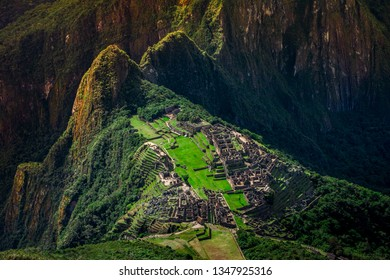 Unique aerial view on the Machu Picchu / Huayna Picchu mountain with Incan sacred city ruins during the sunset.