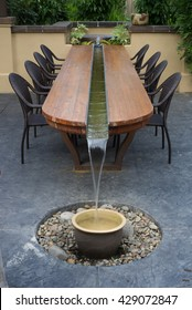 A unique, artistic patio table with a water feature running through its center.