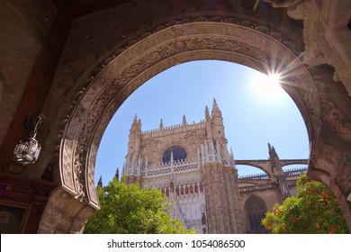 Unique and beautiful view through arched pathway looking at Seville Cathedral and orange trees in the building's courtyard. Nice sunburst on arched opening with a bright blue sky in the background.
