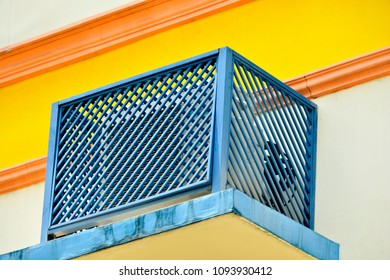 Unique blue metal grill casing protecting an external air conditioning compressor on the side of an apartment building