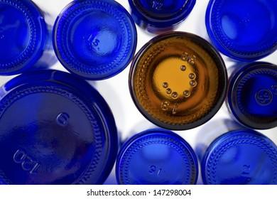 A unique brown glass bottle amongst several different size cobalt blue glass bottles