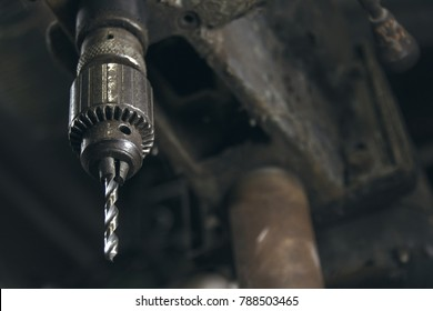 A unique close up angle of an old drill press with weathered paint. The drill bit is in focus and the rest of the press is in the background out of focus.