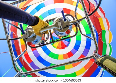 A unique closeup, straight up view of the inside of a bright, multicolored hot air balloon in a blue sky. The gloved hand of the pilot is grasping a burner control handle.