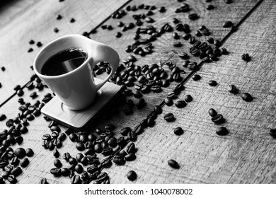 Unique design white espresso cup with black coffee beans. black and white photography on wood or wooden surface or table