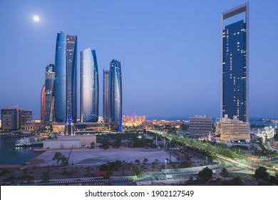 A unique and different perspective of skyscraper towers and cityscape skyline of Abu Dhabi, UAE at night under moonlight.