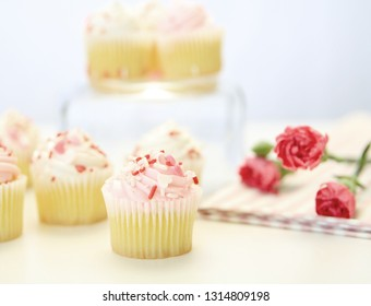 A unique display of cupcakes and pink roses on a blurred background.