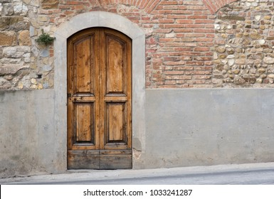 Unique door in stone wall of medieval town in Tuscany, Italy. Doors in stone, entrances through the supporting walls.