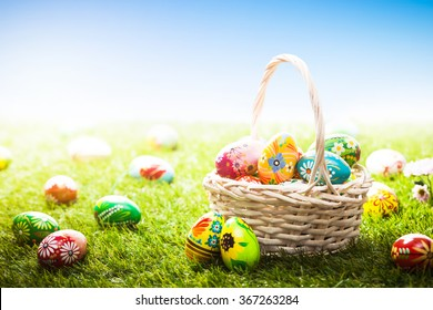 Unique hand painted Easter eggs in basket and lying on grass, blue sky. Traditional decoration in sun light