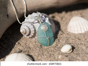 Unique handmade aqua marine sea glass jewellery, with a silver chain on a rustic sand and driftwood background