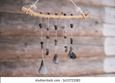 Unique handmade wind chime made of branch and black ceramic bells on log house background