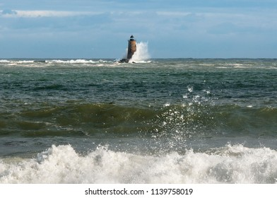 Unique high tide causes huge waves to break along the shore and around a stone lighthouse in the distance in Maine.