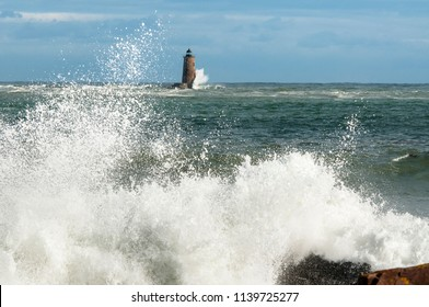Unique high tide causes large waves to break around the shore and around a stone lighthouse in Maine.