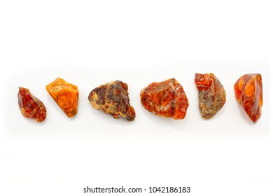 Unique Japanese amber on a white background. A beautiful natural mineral for jewelry. Fossil Resin. Sunstone from Japan. Pieces of amber stone with Bokeh effect. Heap of beautiful stones